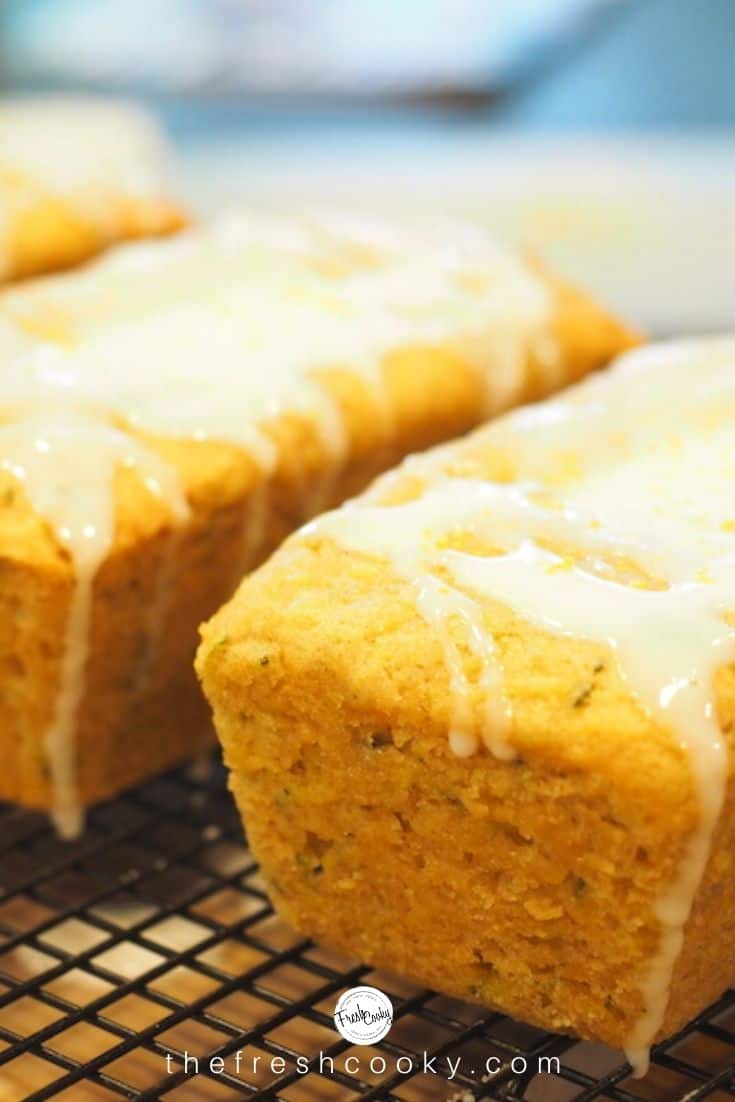 Mini loaves of lemon zucchini bread dripping with lemon glaze atop a cooling rack.