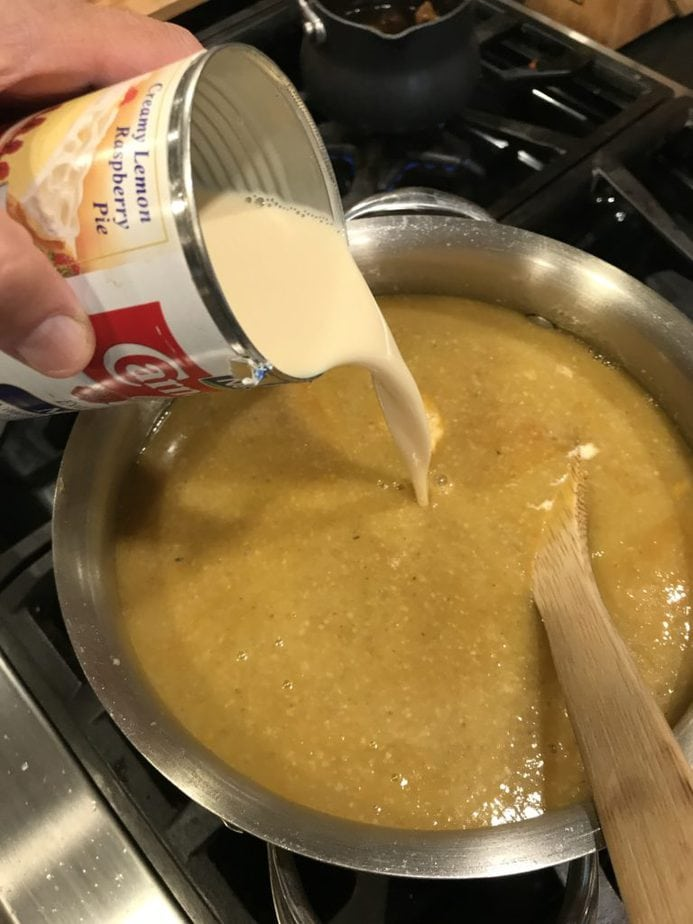 Pouring in evaporated milk into saucepan with pumpkin soup. Wooden spoon on side.
