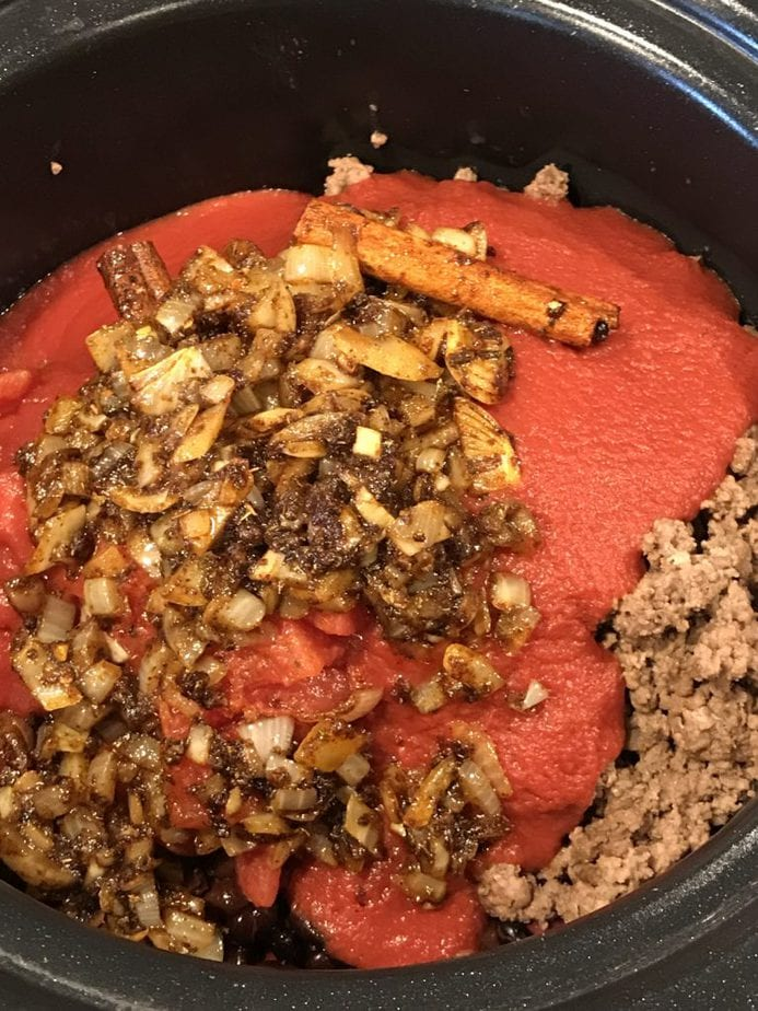 Sauted onions, garlic, spices, cinnamon sticks on top of ground beef, tomato sauce for chili