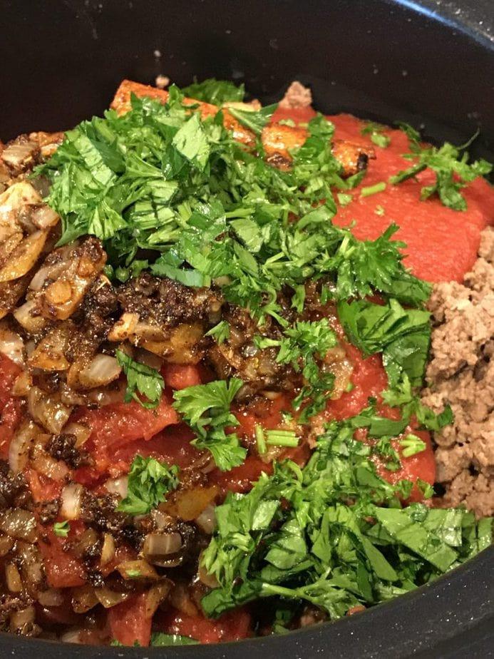 Adding fresh chopped parsley to chili ingredients.
