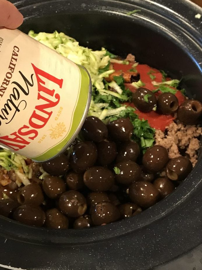 Pouring a can of all natural Lindsay black olives into pot of chili