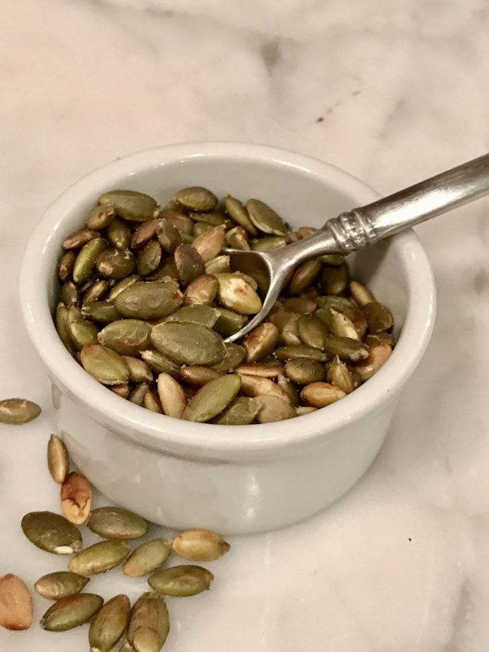 Close up of toasted pumpkin seeds in a small white ramekin with mini silver spoon sitting on marble.