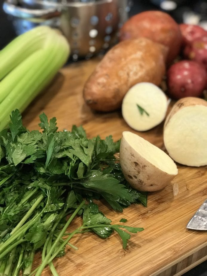 cutting board with parsley, celery, chopped potatoes and washed sweet potatoes and red potato in the background.
