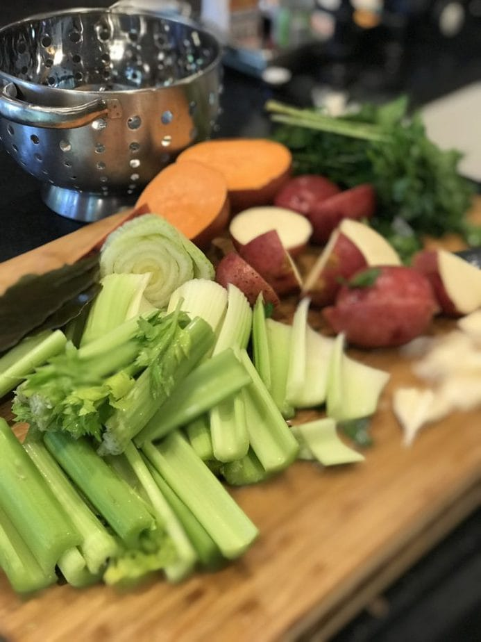 Cutting board with large slices of celery, potatoes, sweet potatoes and garlic with a colander in the background.