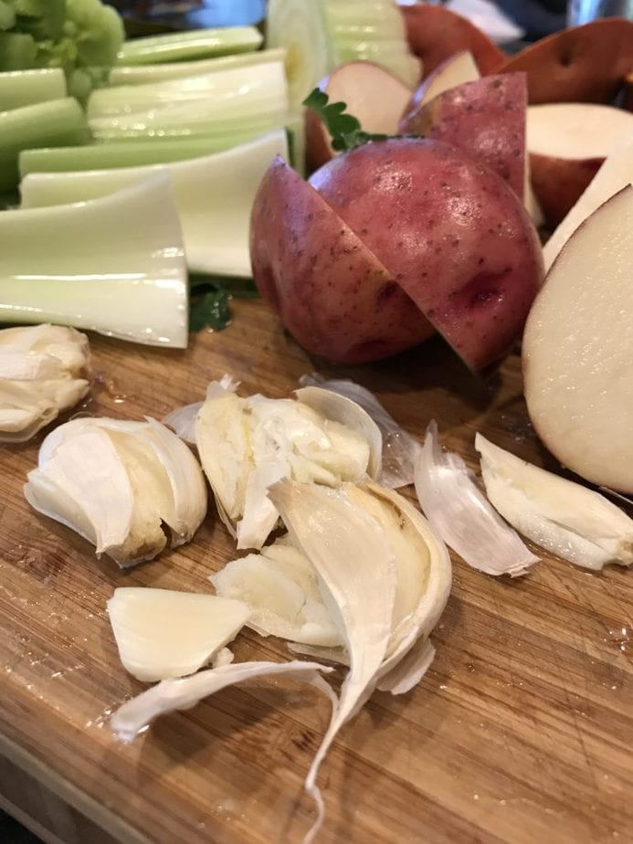 Chopped celery, halved red potatoes, garlic cloves smashed in foreground.
