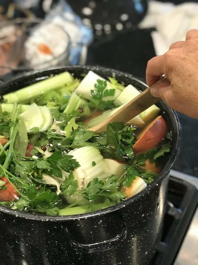 Stirring large black pot of veggies with wooden spoon.