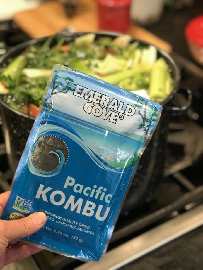 Hand holding a package of Emerald Cove Pacific Kombu seaweed in front of large pot filled with water and veggies.