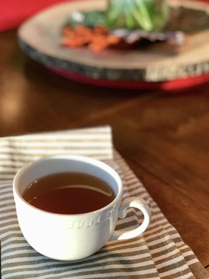 small mug of veggie broth on striped tea towel, sitting on table