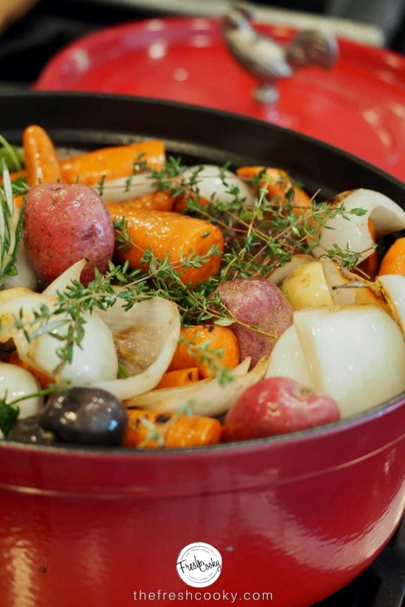 Dutch oven filled with carrots, onions, potatoes, pot roast and broth ready to go in the oven.