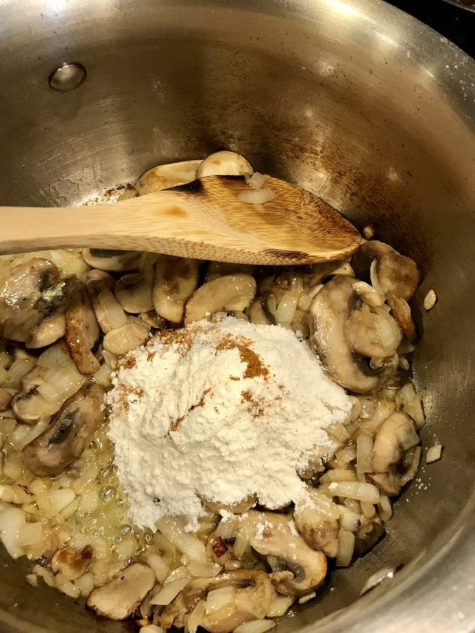 Flour and curry powder added to sauted mushrooms and onions in saucepan.