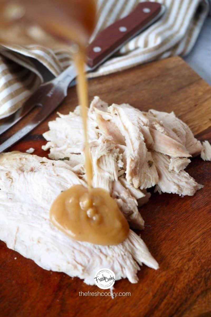 image of sliced turkey pouring giblet gravy on top sitting on a cutting board.