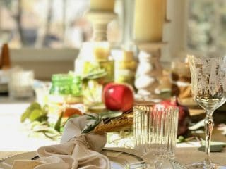 Image of thanksgiving table with candlesticks, china place settings, apples, natural decor and more.