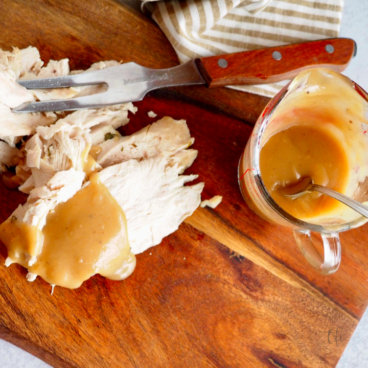 Easy turkey giblet gravy square image with sliced turkey breast on cutting board poured with rich turkey gravy.