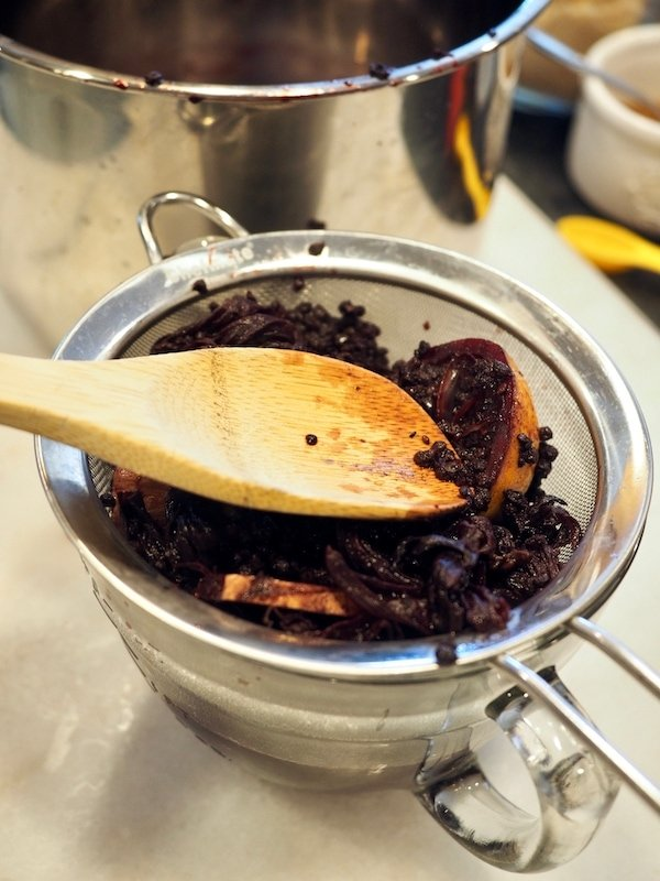 Elderberries, organes masicated after cooking in a sieve with wooden spoon pressing down catching juice in mixing bowl.