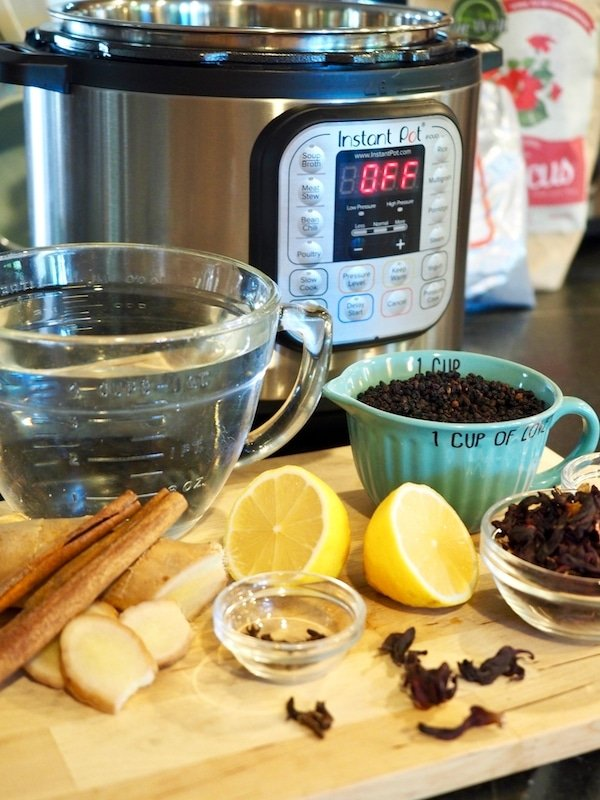 Instant Pot with 4 qts of water, 1 cup of elderberries in turquoise measuring cup, halved lemons, hibiscus flowers, cloves in small glass bowl, sliced ginger and cinnamon sticks all sitting on wooden cutting board on counter.