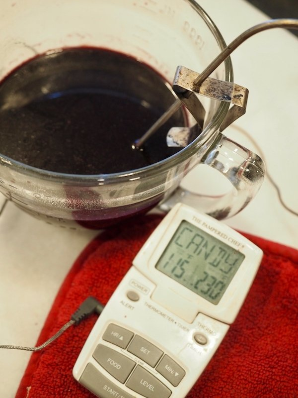 food thermometer (digital) with 115 degrees show and probe inside mixing bowl with elderberry syrup.