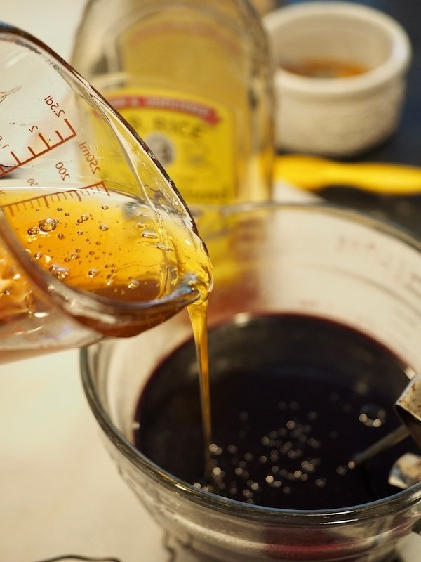 pouring honey into finished and cooled elderberry syrup in large mixing bowl.