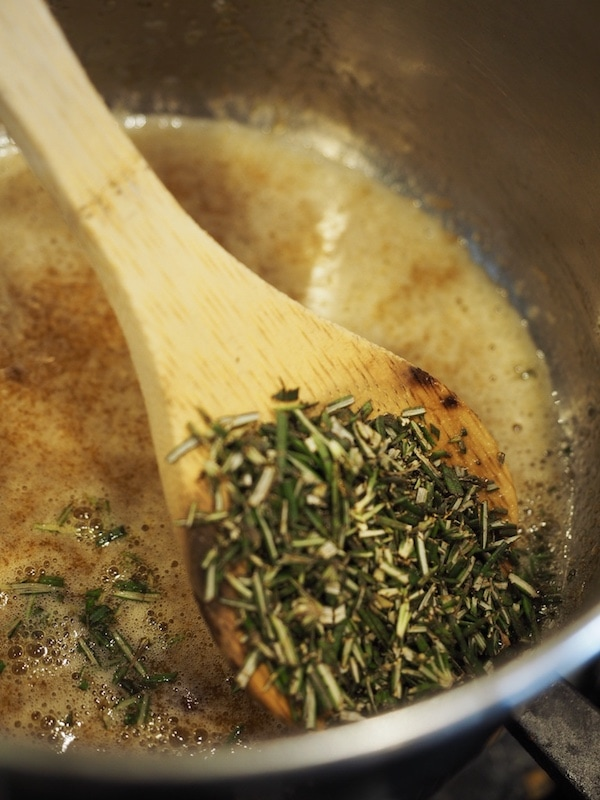 Adding fresh chopped rosemary to butter, sugar slurry for rosemary cashews.