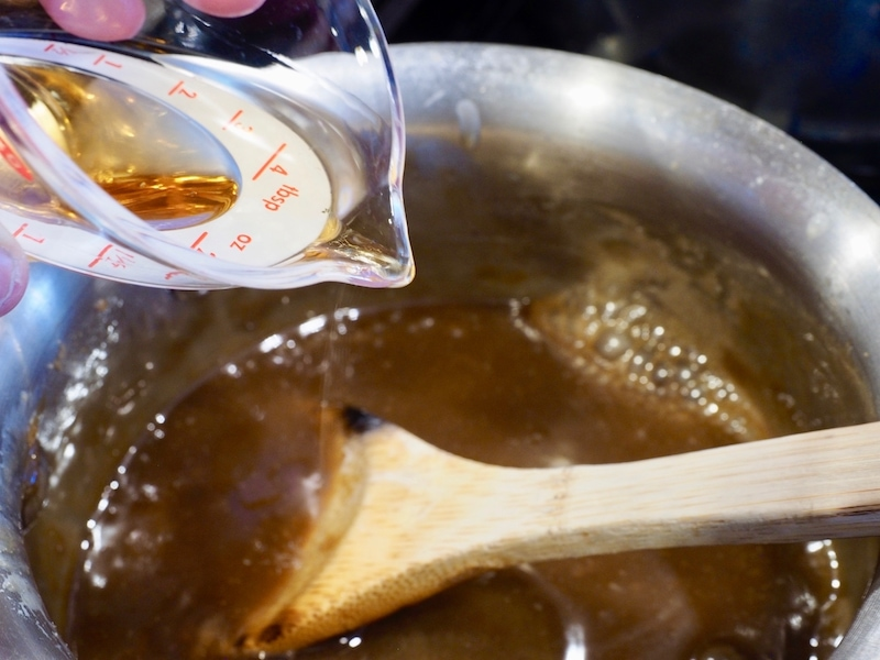 Pouring in bourbon to caramel sauce
