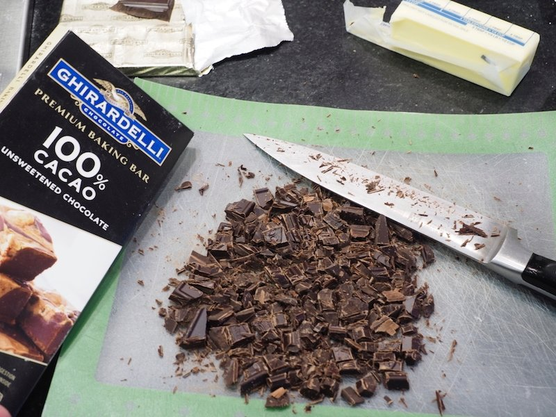 Chopped ghirardelli 100% cacao unsweetened chocolate bar and chopped chocolate on cutting board with knife.  | thefreshcooky.com