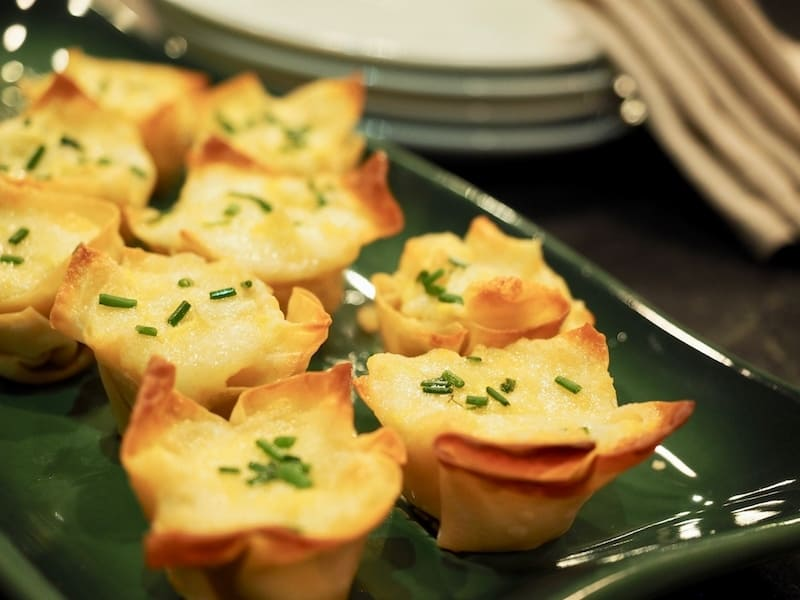 Finished artichoke cheese wontons on green ceramic tray with chopped chives sprinkled on top. Artichoke Cheese Wontons | www.thefreshcooky.com