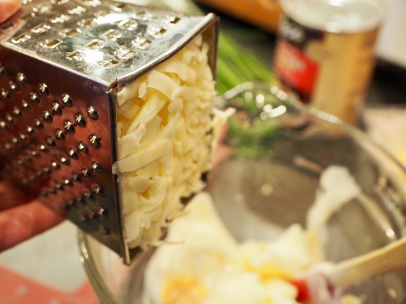 Shredded cheese in a grater going into mixture. Artichoke Cheese Wontons | www.thefreshcooky.com