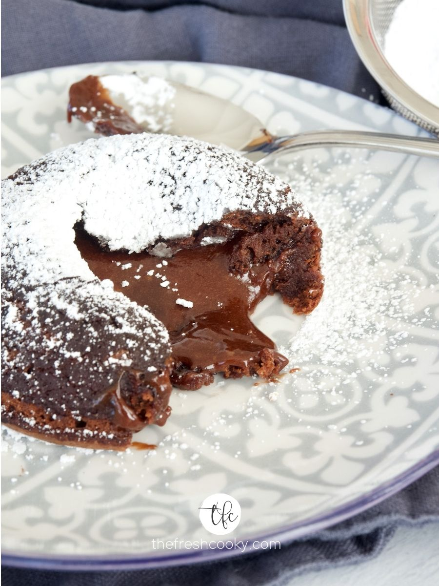Easy Lava Cake on pattered gray and blue plate with spoon in background, easy lava cake recipe shown open with oozing chocolate sprinkled with powdered sugar