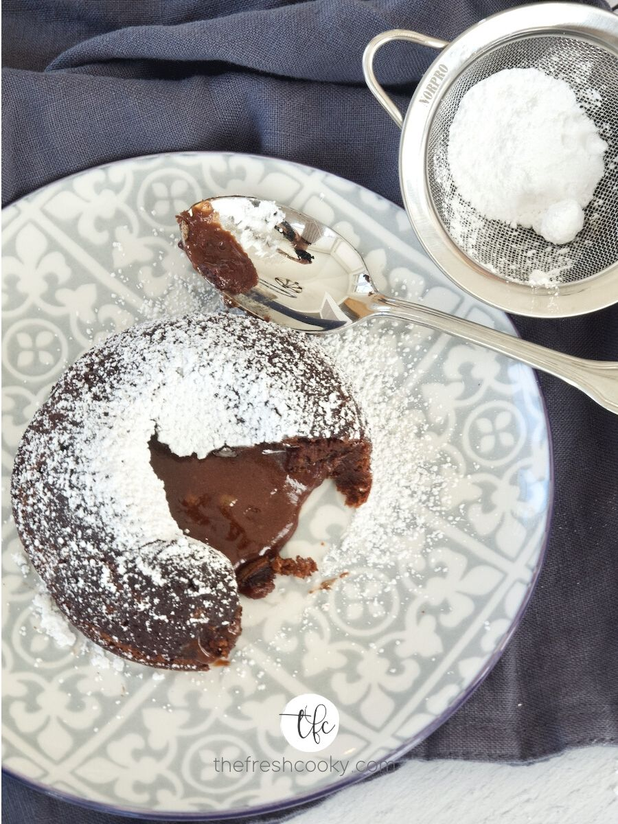 """lava cake on gray patterned plate open with oozing """"lava"""" dusted with powdered sugar with blue napkin below."""