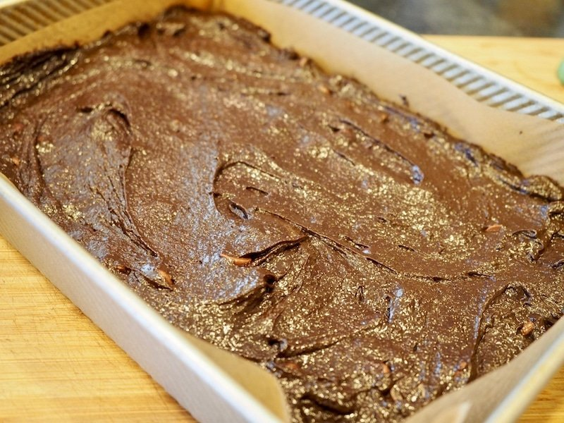 brownie batter spread into 9x13 inch pan lined with parchment paper