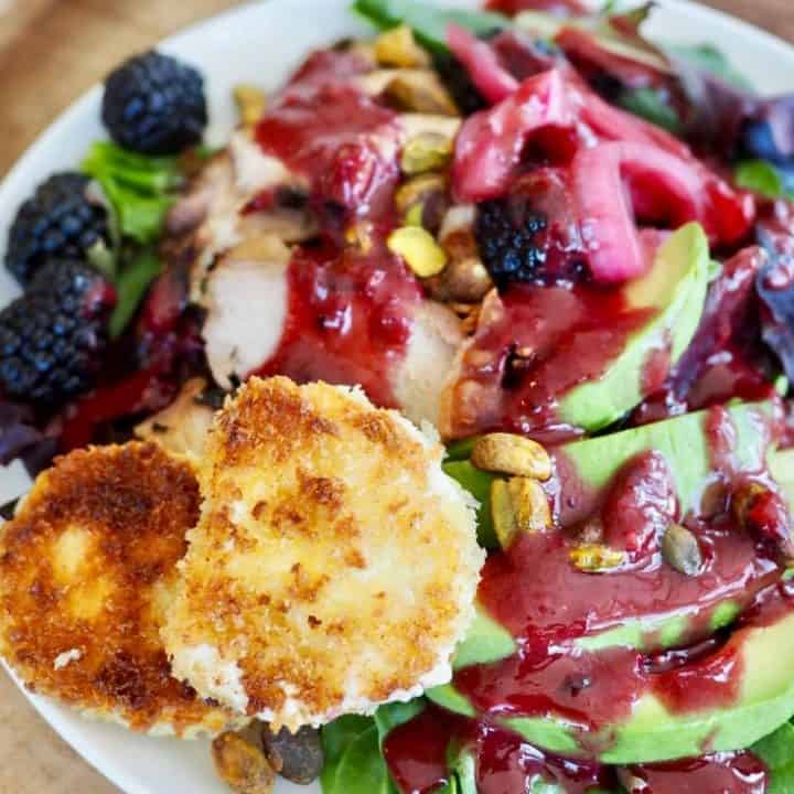 white plate on sliced wood charger with a bright salad with greens, avocados, chicken, blackberries and a luscious blackberry vinaigrette along with two discs of fried goat cheese