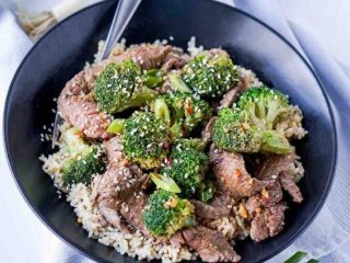 Easy Beef and Broccoli image in black bowl with green onions on tea towel underneath, spoon in bowl.