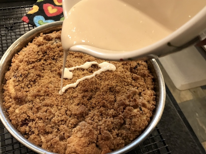 Baked Blueberry Crumb Cake with mixing bowl pouring glaze over the top of the cake.