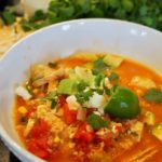 Super easy tortilla soup is perfect for any chilly (or summer) day and is done in 30 minutes or less, or easily adapts to a slow cooker. It's a hearty, flavorful soup using chicken, broth, tomatoes and veggies and is fully customizable with your favorite toppings. #thefreshcooky #tortillasoup #chicken #soup #slowcooker #30minutemeal
