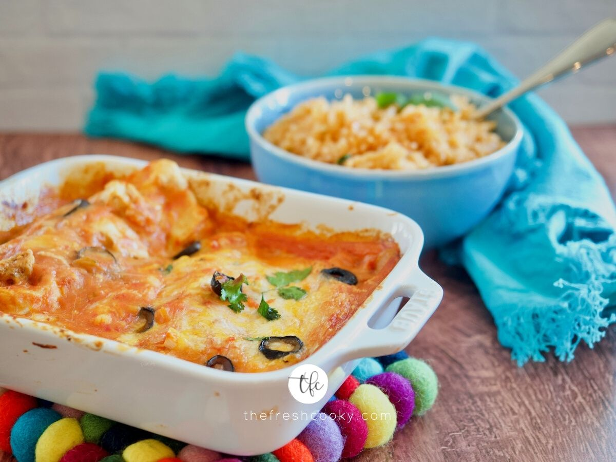 FB image with casserole dish filled with cheesy enchiladas and bowl of spanish rice in background.