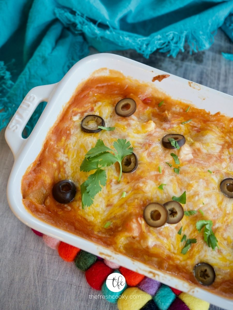 top down shot of cheese enchiladas with brightly colored hot pad beneath, sprinkled with sliced black olives.