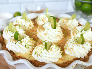Square image of whole easy key lime pie with dollops of whipped cream and decorated with wedges of key limes.