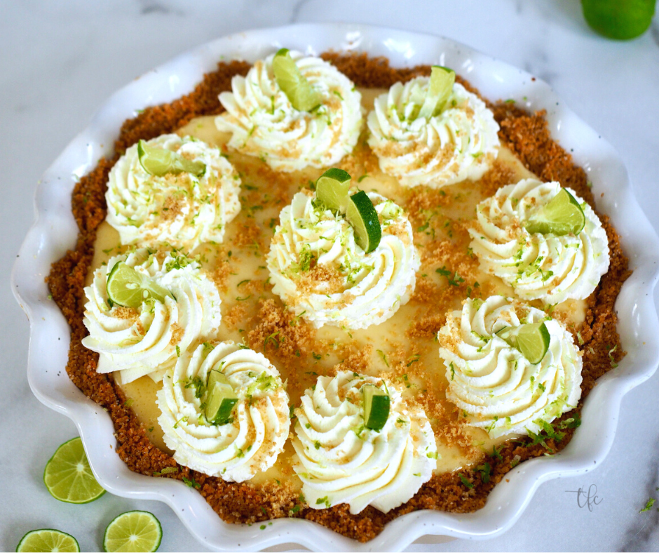 Easy Key Lime Pie image of top down shot of decorated key lime pie with swirls of whipped cream and decorated with wedges of lime.