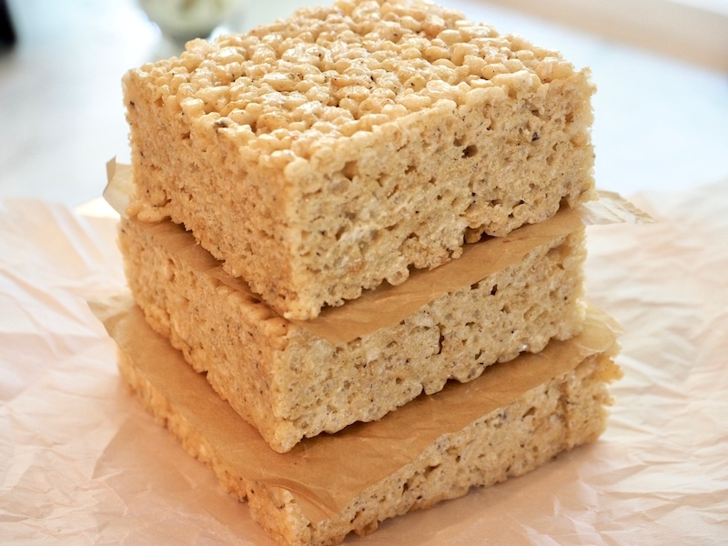 Stack of three gigantic squares of rice crispie treats with parchment paper between them.