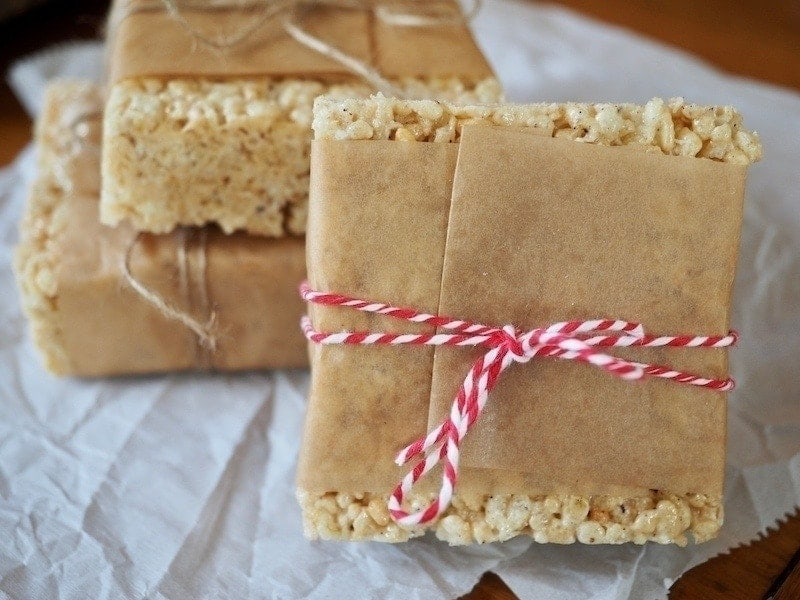 Gigantic squares of rice crispie treats with natural parchment paper tied around tied with string for presentation.