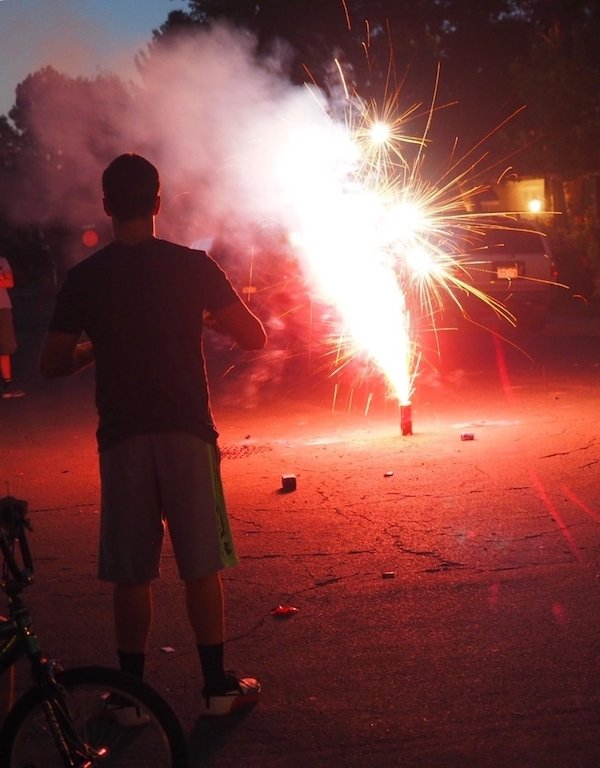 Teenage Boy standing in front of a fountain firework on the 4th of July.