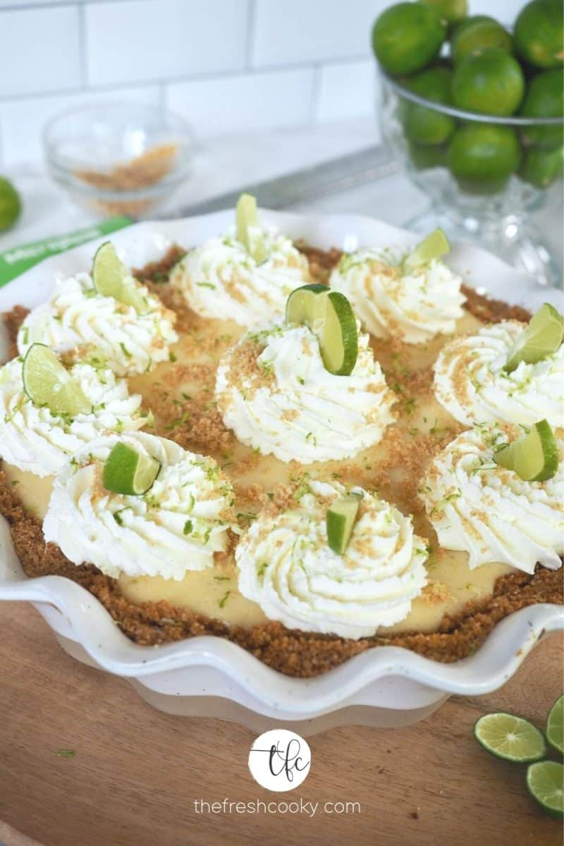 image of key lime pie on wooden plate with limes in background. Individual dollops of whipped cream marking slices on pie