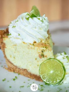 Slice of creamy key lime pie, on white place with two swirls of whipped cream, slice of lime and lime zest sprinkled on top.
