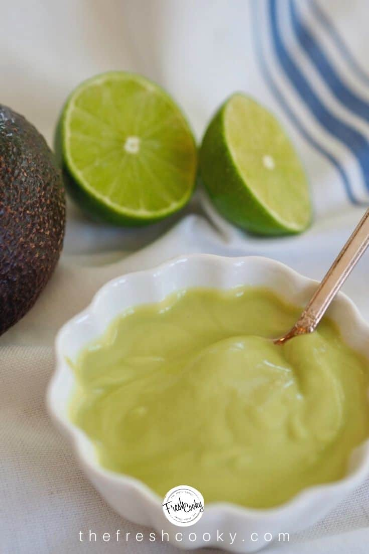 white scalloped bowl with avocado lime dressing in it, with spoon and limes sliced behind.