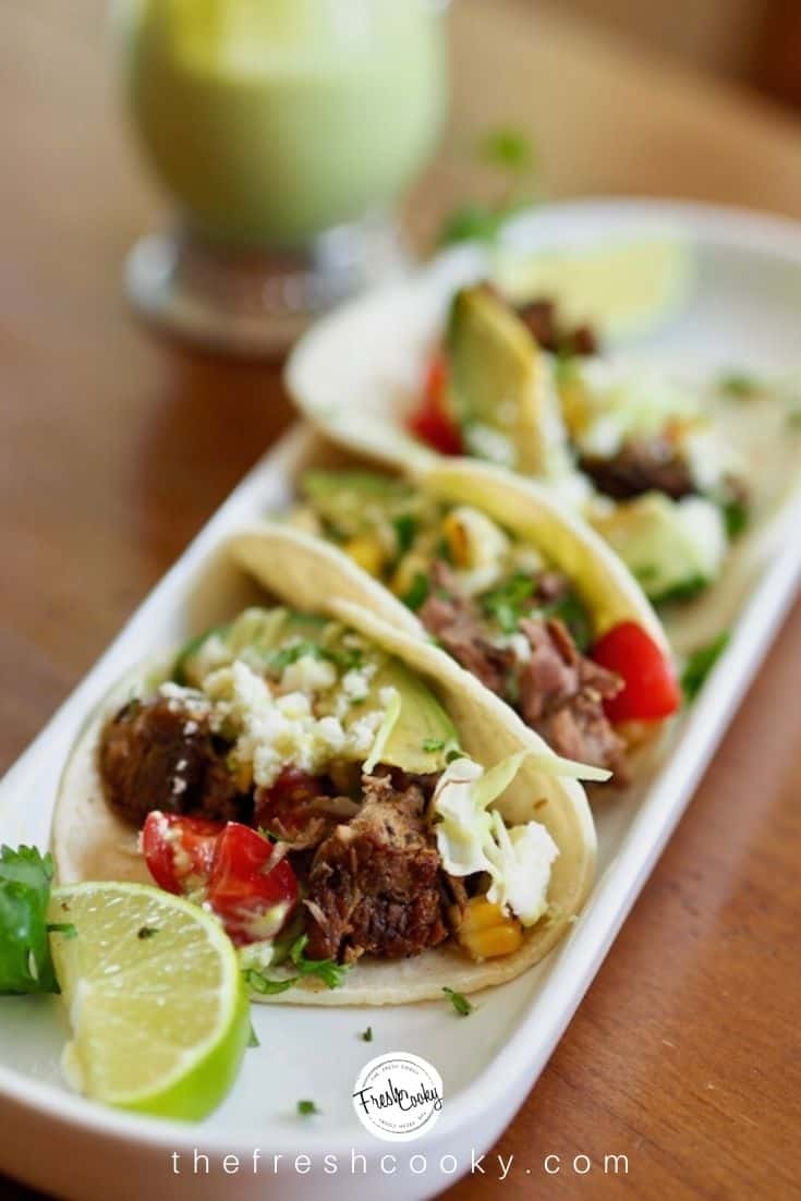Pinterest image with plate of barbacoa beef street tacos with lime, avocado and cilantro.