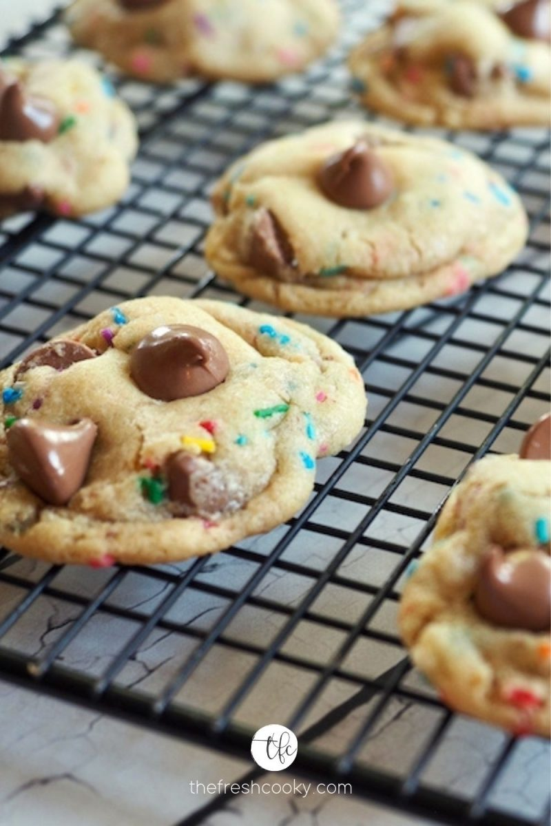 Cake Batter Chocolate Chip Cookies cooling on wire rack with melty chocolate chip cookies.
