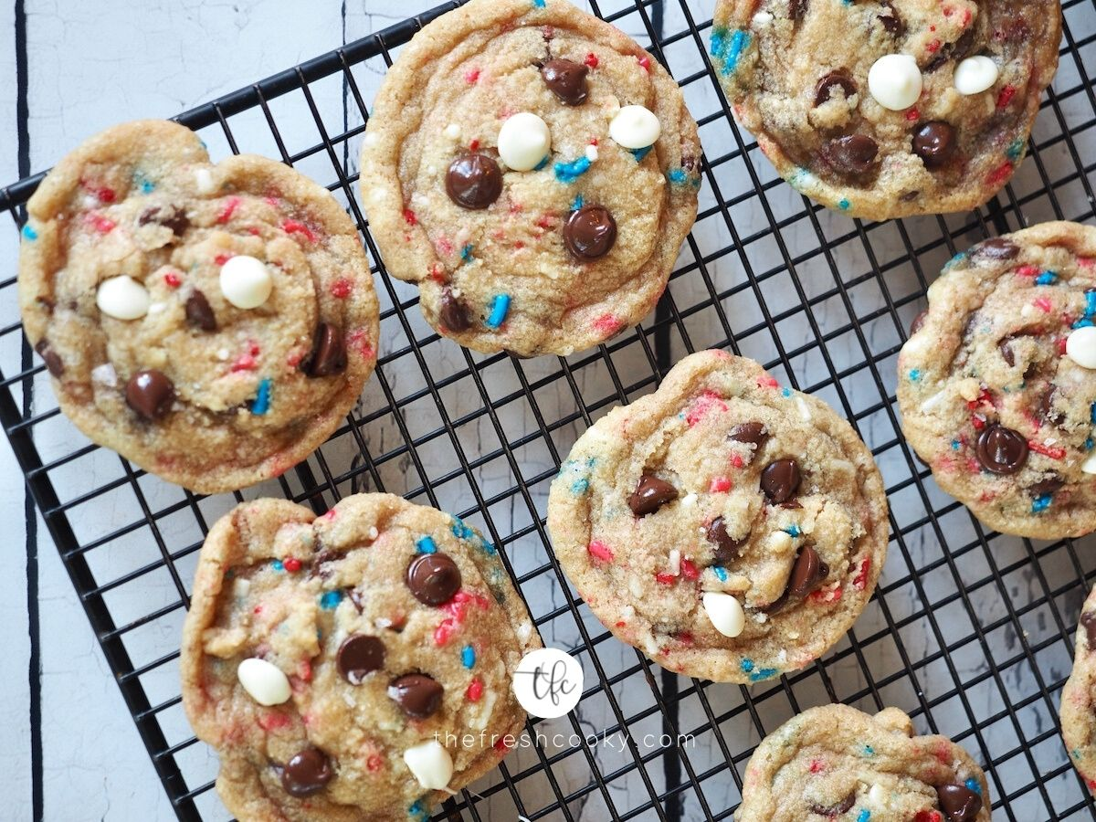 Patriotic Cake Batter Cookies on wire rack with chocolate chips and white chocolate chips and red, white and blue sprinkles.
