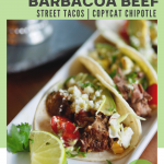 Crock Pot Mexican Barbacoa Beef for street tacos with image of several barbacoa beef tacos with toppings on a white plate.
