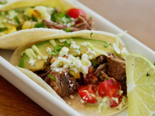 Square image of Mexican Barbacoa Beef in form of street tacos sitting on a white plate with cheese, avocado, tomatoes and lime.