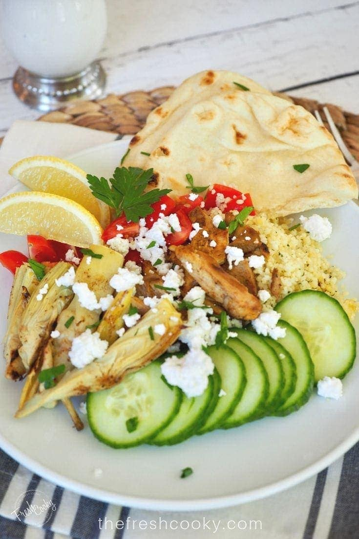 plate filled with sliced chicken shawarma on a bed of cous cous with fresh tomatoes, cucumbers, feta cheese and grilled artichoke hearts, with some naan bread and slices of lemon.