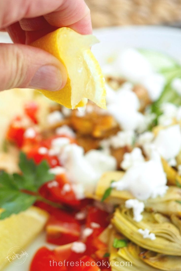 Squeezing a lemon onto  a bowl of grilled chicken shawarma.